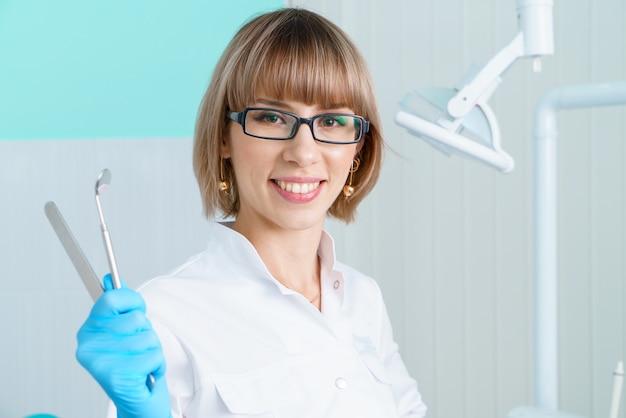 白衣とメガネで歯科医院の背景にツールを保持している女性の歯科医はth ...