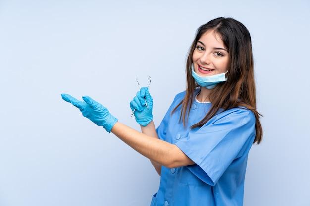 青い壁を越えて手を側に拡張するツールを保持している女性歯科医