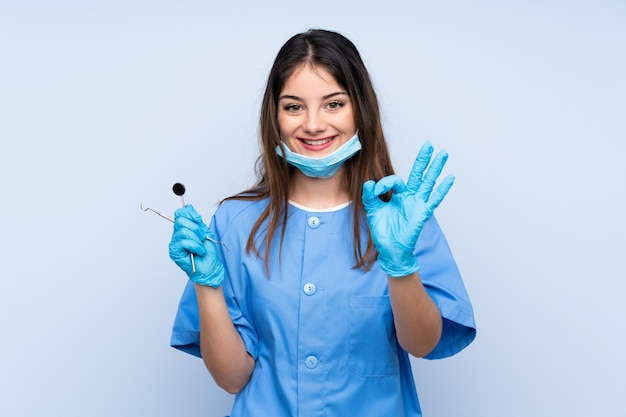 Woman dentist holding tools showing an ok sign with fingers