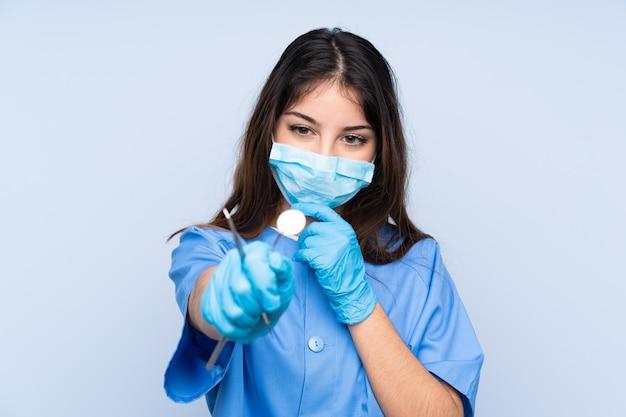 Woman dentist holding tools