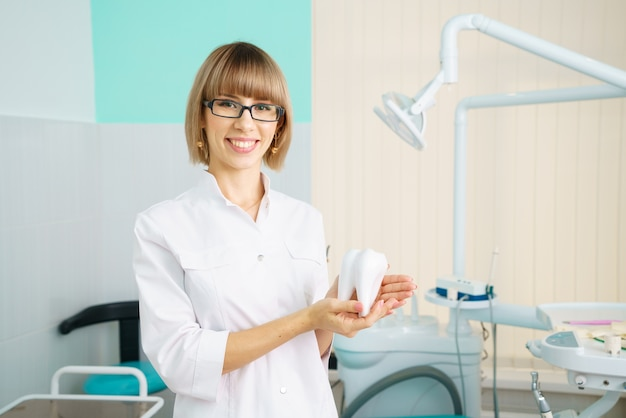 Woman dentist in office holding tool as concept of care for the oral cavity
