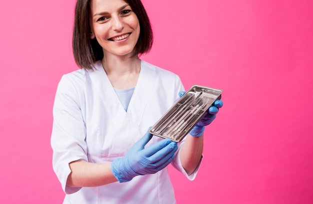 女性歯科医が滅菌歯科用器具のパッケージを開封