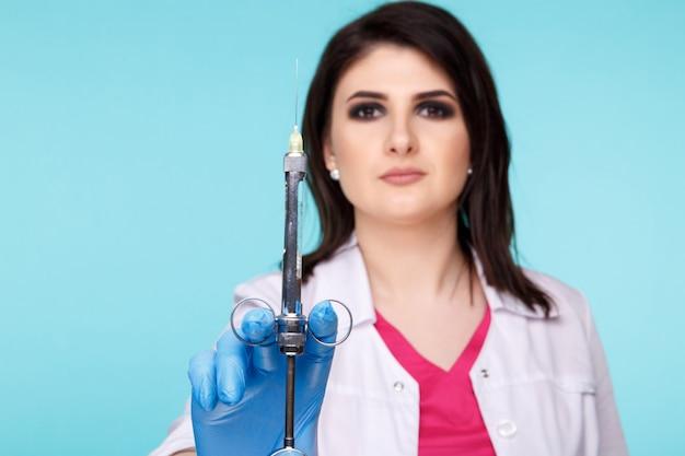 青い背景の上に分離された歯科ツールでポーズをとる女性歯科医。