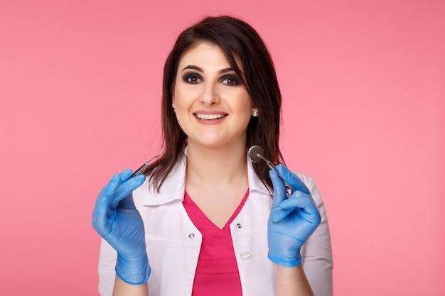 ピンクの背景の上に分離された歯科ツールでポーズをとる女性歯科医。