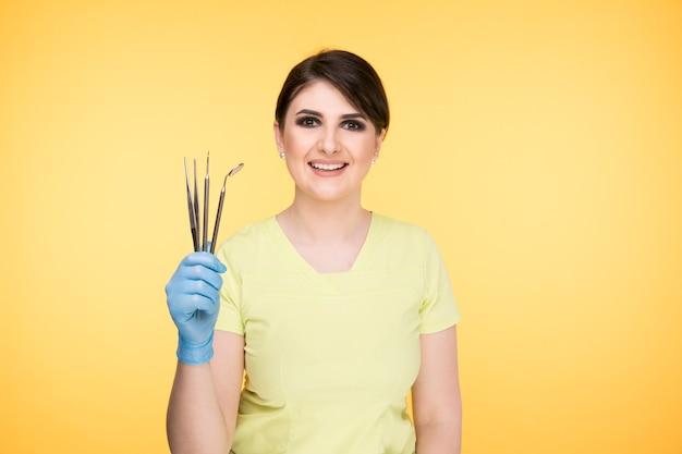 노란색 배경 위에 격리된 치과 도구를 들고 포즈를 취하는 여성 치과 의사.