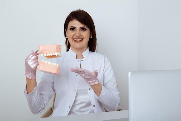 Женщина-дантист, сидя за столом в офисе с изолированным стоматологическим персоналом.