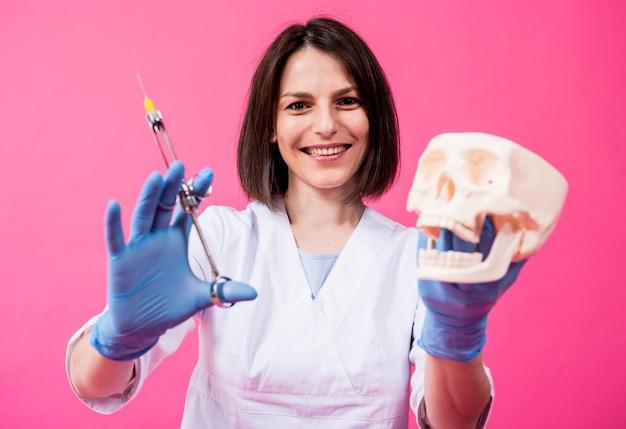 相乗り注射器を持った女性歯科医が人工頭蓋骨の歯茎に麻酔薬を注入します