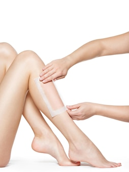 Woman depilating her legs by waxing -