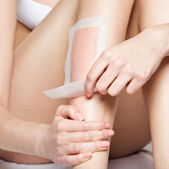 Woman depilating her legs by waxing