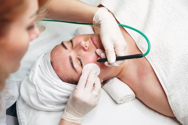 プロの電気焼灼を準備する女性皮膚科医