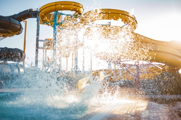 An woman an descended from a large, high yellow slide into a pool of clear, clear water and created more spray