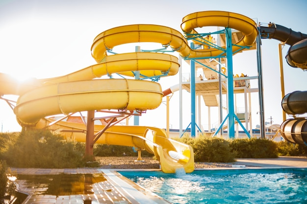An woman an descended from a large high yellow slide into a pool created spray