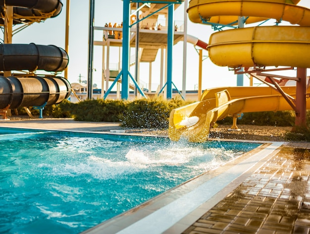 An woman an descended from a large, high yellow slide into a pool of water and created more spray