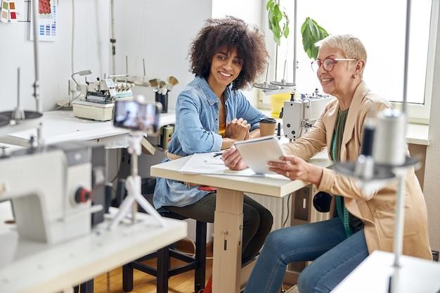 女性デザイナーとアフリカ系アメリカ人のアシスタントがワークショップで現代のミシンを見る