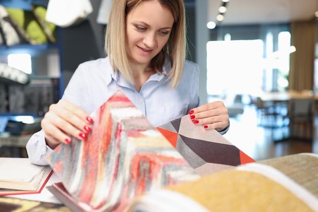 여성 디자이너 데코레이터는 직물 카펫을 직물로 자수하는 커튼용 직물을 선택합니다.