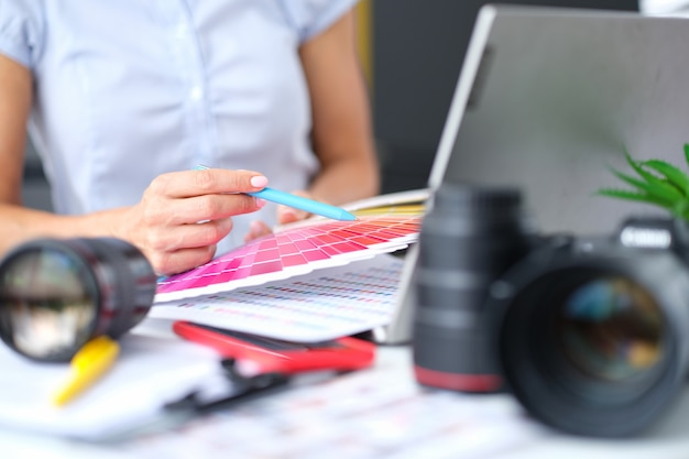 여성 디자이너는 책상에서 색상 팔레트를 들고 인테리어 컨셉의 색상과 음영을 선택합니다.