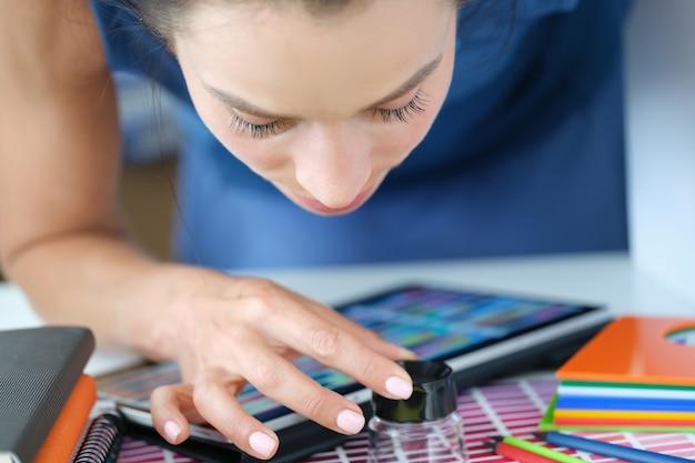 돋보기를 통해 종이 팔레트의 색상 샘플을 보고 있는 여성 디자이너. 색상 일치 개념 선택에 대한 디자이너 지원