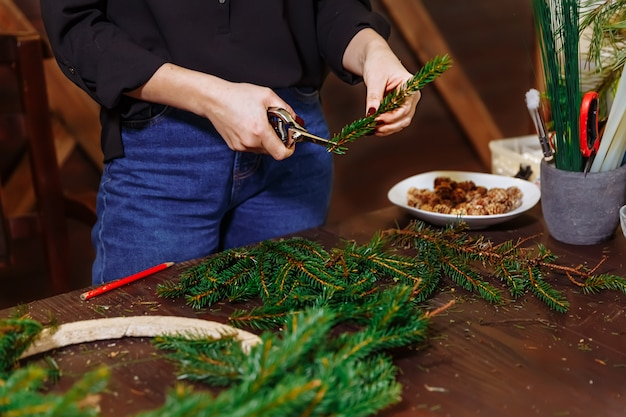 Woman designer preparing christmas evergreen tree wreath, manufacturer of christmas decor with their own hands, christmas wreath for the holiday, the new year celebration, closeup view.