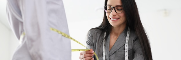 女性デザイナーは、アトリエの個別の仕立てのコンセプトでクライアントから測定を行います