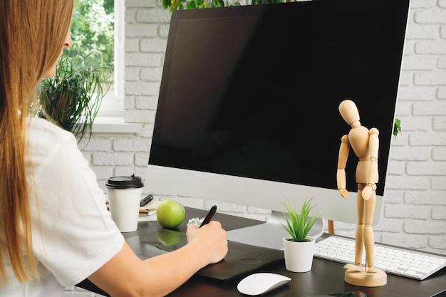 사무실에서 일하고 그래픽 태블릿을 사용하는 여성 디자이너
