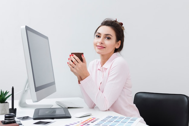 Woman at desk enjoying a cup of coffee