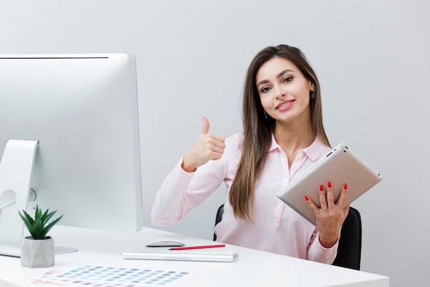 Woman at desk giving thumbs up while holding tablet