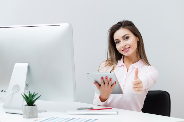 Woman at desk holding tablet and giving thumbs up