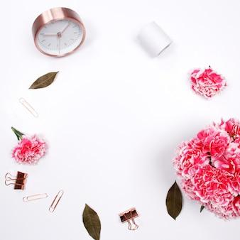 白い背景にピンクのカーネーションの花と女性のデスクワークスペースのフレーム。