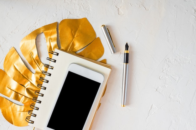 Woman desktop. golden tropical monstera leaf, blank notepad, white smartphone and pen on white concrete background.