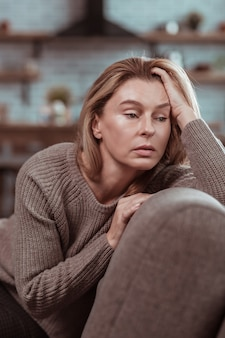 Woman in despair. dark-eyed appealing mature woman sitting on sofa and feeling in despair