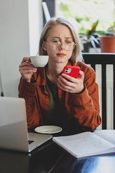 홈 오피스에서 컴퓨터와 휴대폰을 사용하는 여성 개발자
