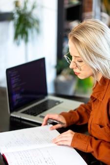 Разработчик женщина, работающая с компьютером в домашнем офисе