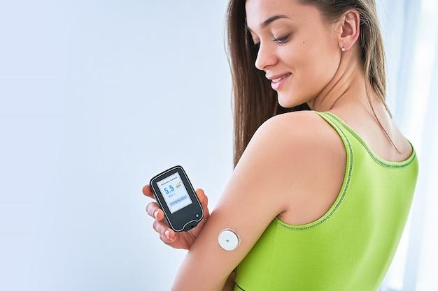 Женщина-диабетик контролирует и проверяет уровень глюкозы с помощью дистанционного датчика. непрерывный мониторинг уровня глюкозы без крови. медицинские технологии в лечении сахарного диабета