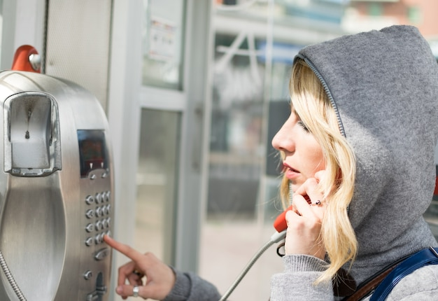 Woman dialing a payphone