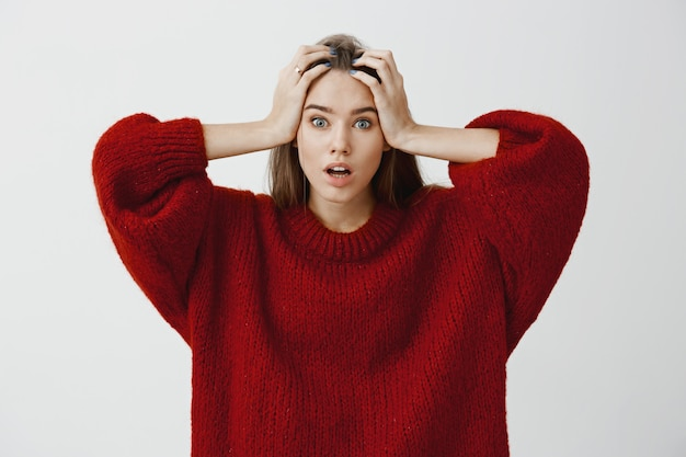 女性は心配して問題を解決する方法を知りませんでした。灰色の壁を越えてトラブルに直面して緊張を感じて、頭に手を繋いでいるスタイリッシュな赤いルーズセーターでショックを受けた美しい女性を強調