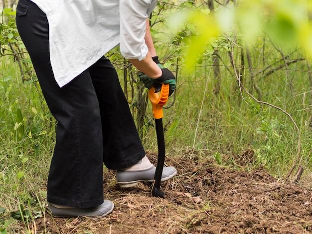 Женщина копает в своем саду