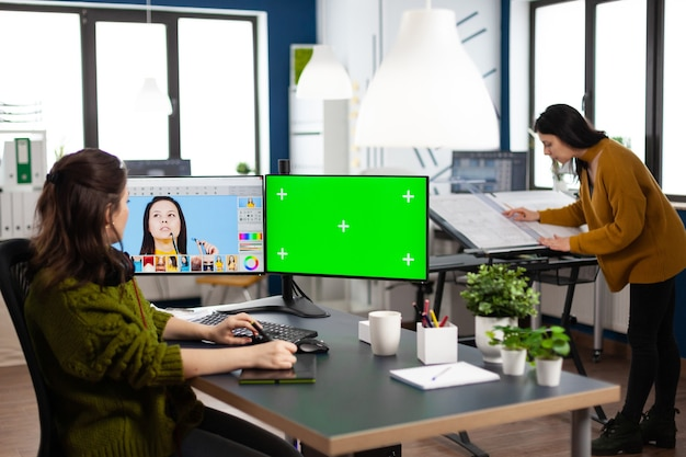 Woman digital artist working editing creative photo using greenscreen chroma key isolated display