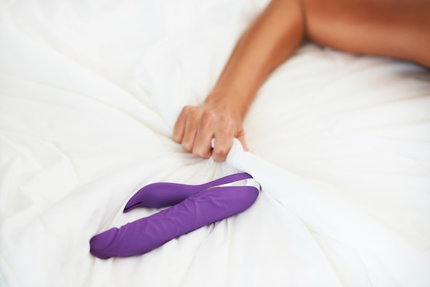 Woman and dildo in bed