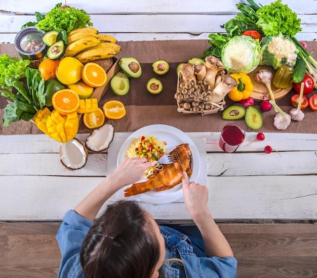 Donna al tavolo da pranzo con una varietà di alimenti biologici sani, vista dall'alto. il concetto di sana alimentazione e celebrazione