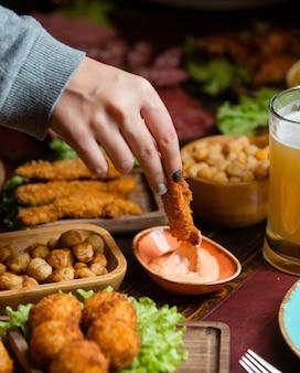 Женщина, окуная куриный крокет в соус в пивной настройке с орехами