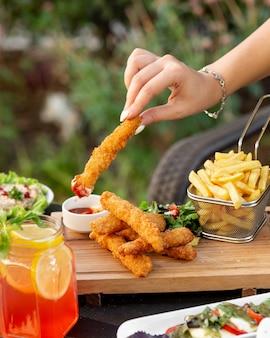 Donna che immerge le crocchette del dito di pollo nel ketchup