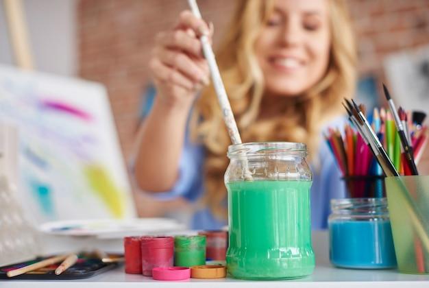 Woman dipping paintbrush in bottle