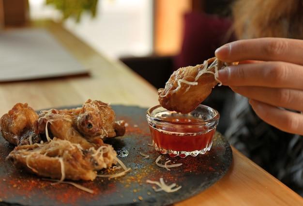 テーブル、クローズアップでソースにおいしいバーベキューの翼を浸している女性