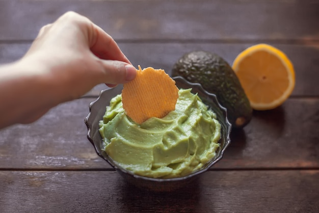 Woman dips a cracker in the mexican sauce guacamole in bowl, avocado and lemon on dark background.