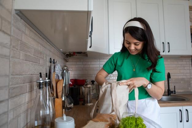 Женщина разбирает покупки дома кухня домохозяйка концепции