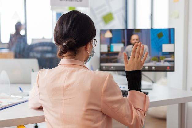 Женщина обсуждает проект работы с бизнесменом во время удаленного видеозвонка в новом обычном офисе во время глобальной пандемии covid19, носит защитную маску для защиты от инфекции.