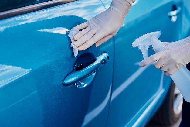 車のドアのハンドルを抗菌スプレーで消毒する女性