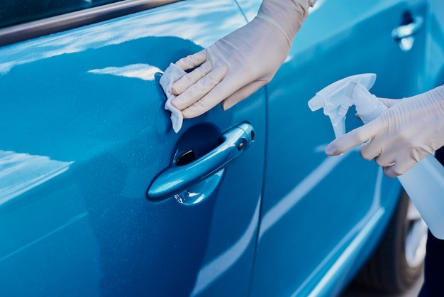 Woman disinfecting car door handle with an antibacterial spray