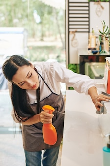 Woman disinfecting coffeeshop counter