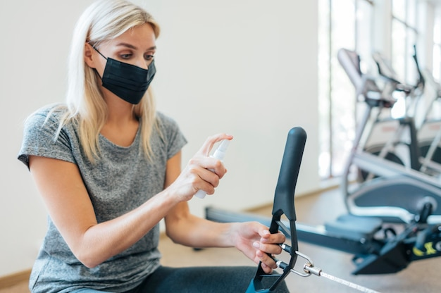 Woman disinfecting gym equipment during pandemic